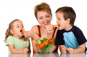 Женщина кормит детей овощами для укрепления здоровья