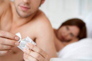 Мужчина с презервативом в руках